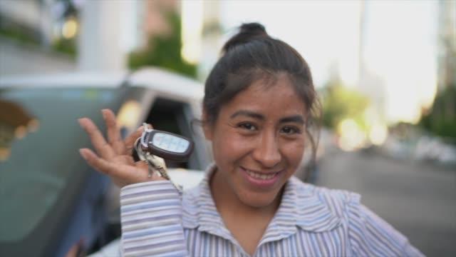 彼女の新しい車のキーを示す幸せなラテンの女性 - 車のキー点の映像素材/bロール