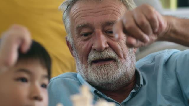 vidéos et rushes de happy life: grand-père jouant avec son petit-fils - senior dynamique