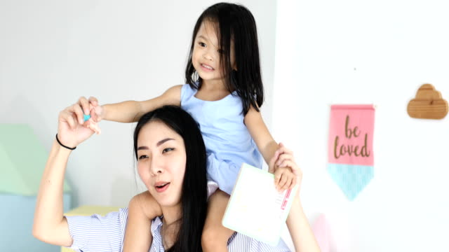 happy little asian girl on the back of her mother in the house - piggyback stock videos and b-roll footage