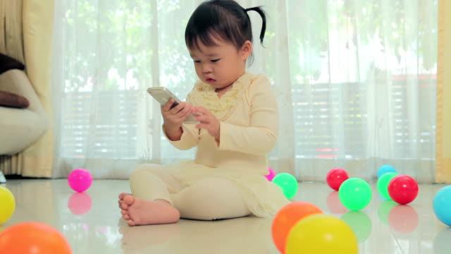 vídeos de stock e filmes b-roll de pequena menina asiática feliz com o telemóvel em casa - pequeno