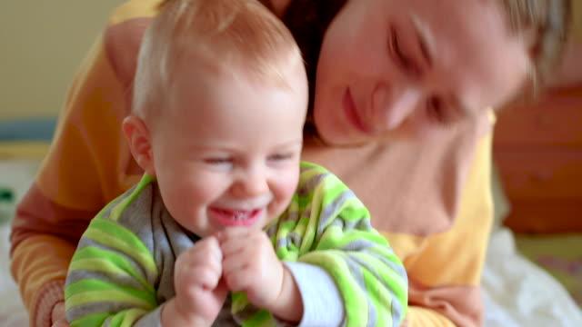 Glada lilla bebis och hans mamma