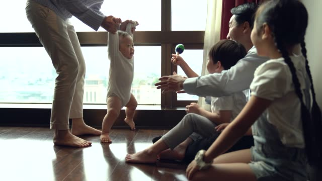 happy little baby learning to walk with mother at home with his parent cheer up as foreground. family, child, childhood and parenthood concept. - steps stock videos & royalty-free footage