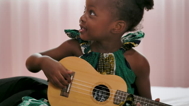 vídeos de stock, filmes e b-roll de menina negra feliz tocando guitarra com a mãe no quarto. - cantar