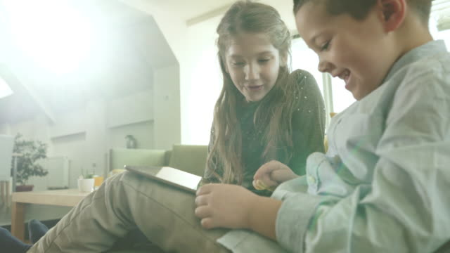 happy little boy and girl using digital tablet while relaxing at home. - touchpad stock videos & royalty-free footage