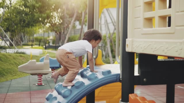 happy little boy down slide in park - nursery school child stock videos & royalty-free footage