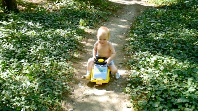 glücklich kleiner junge mit seinem kunststoff-spielzeug-auto - spielzeug stock-videos und b-roll-filmmaterial