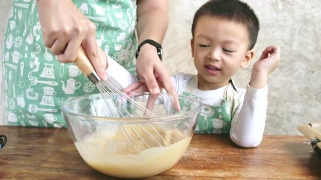 stockvideo's en b-roll-footage met gelukkige weinig jongen die moeder helpt in keuken die ingrediënten mengt die chocoladecupcakes bakken die recept thuis voorbereiden - zelfgemaakt
