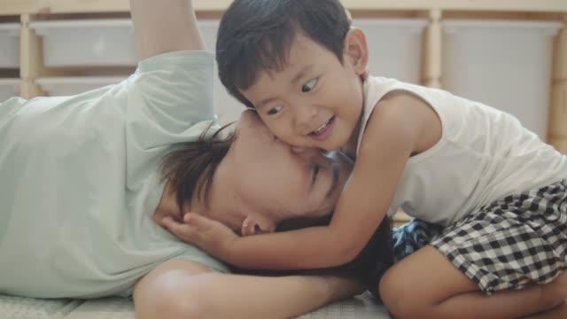 幸せな小さな男の子は、朝のベッドで母をキス - living room点の映像素材/bロール