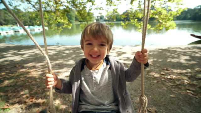 happy little boy on swing - solo un bambino maschio video stock e b–roll