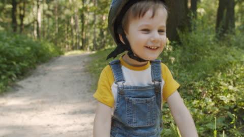vidéos et rushes de petit garçon heureux conduisant son vélo dans le parc d'été - 4 5 ans