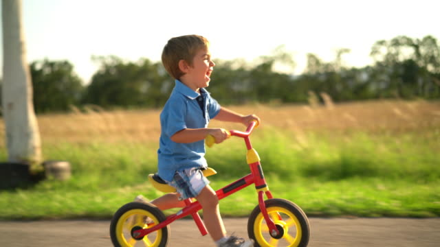 happy little boy riding his bike - short hair stock videos & royalty-free footage