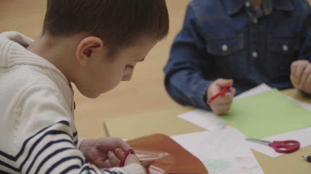 4k: happy little boy using scissors in kindergarten. - preschool child stock videos & royalty-free footage