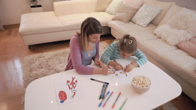 glückliche kleine mädchen und ihre mutter färbung auf ein stück papier zu hause. - gekritzel zeichnung stock-videos und b-roll-filmmaterial