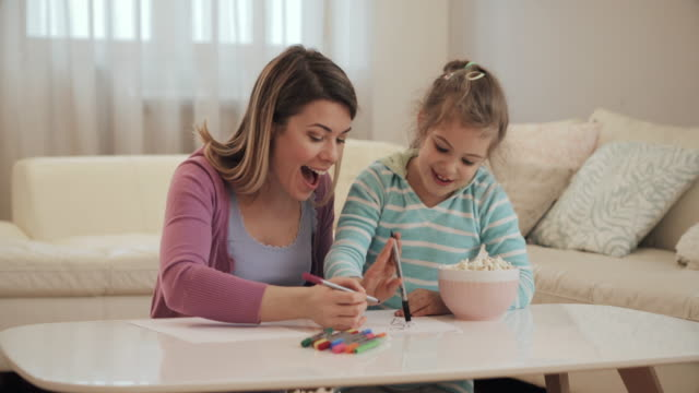 Happy little girl and her mother drawing on the paper and having fun together.