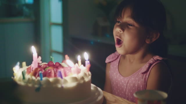 happy little girl blowing out candles on a birthday cake - compleanno video stock e b–roll