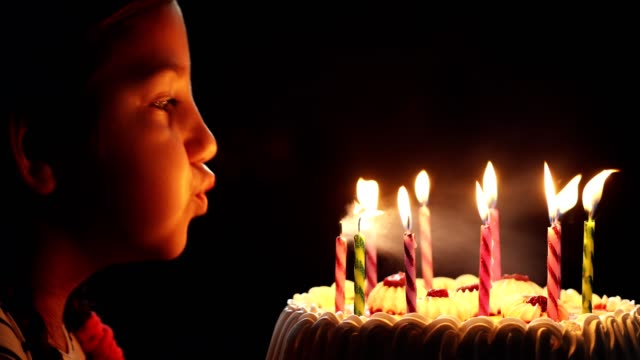 happy little girl blowing out candles on a birthday cake - candlelight stock videos and b-roll footage