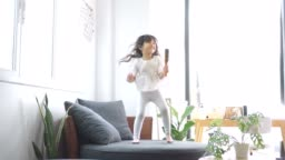 Happy little girl dancing in living room at home