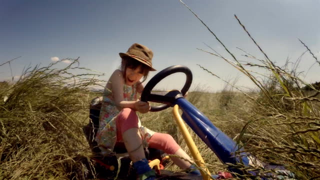 GENDER NEUTRAL KIDS. A Happy Little Girl Drive Go-chart, Off-Road. Happy Memories Of Her Young Days