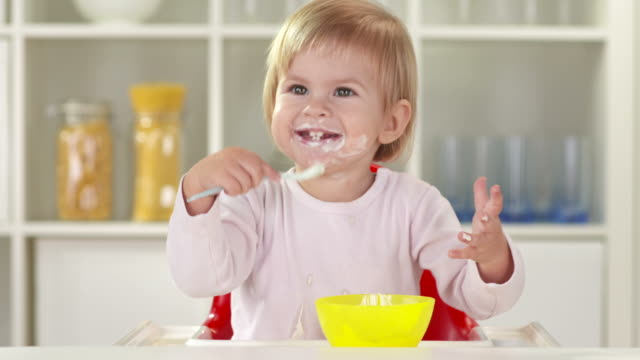 hd: happy little girl eating with spoon - one baby girl only stock videos & royalty-free footage