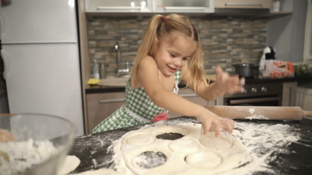 vídeos de stock e filmes b-roll de happy little girl having fun with dough and making round shaped cookies with drinking glass. - balcão de cozinha