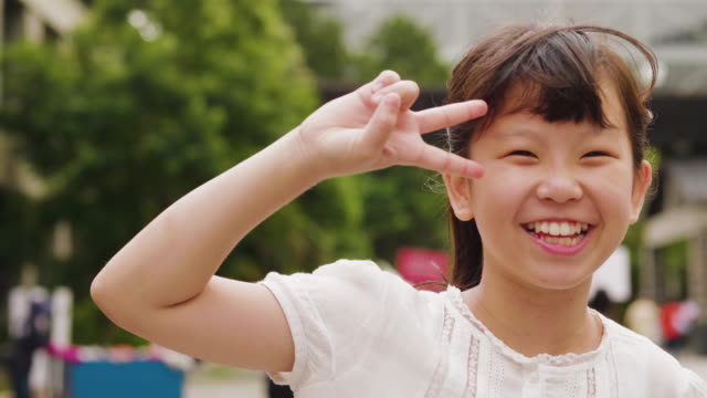 happy little girl in taipei doing the peace sign - taipei stock videos & royalty-free footage