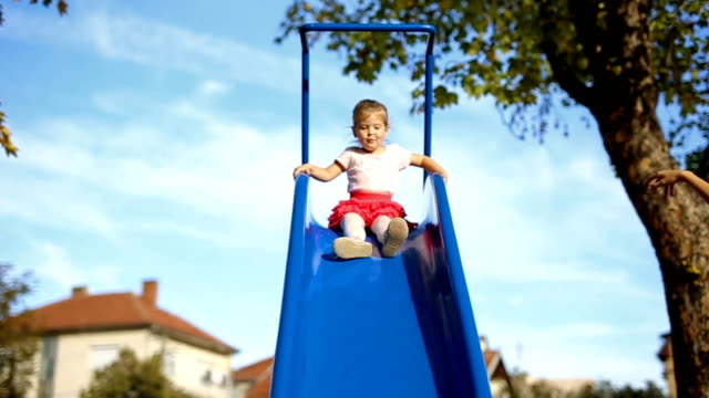 happy little girl on slide in park - parco giochi video stock e b–roll