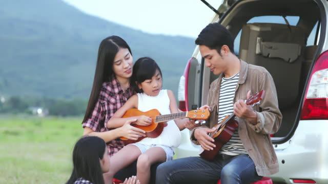 glückliche kleine Mädchen spielt Ukulele mit asiatischen Familie sitzt im Auto für Road Trip und Sommer Urlaub genießen