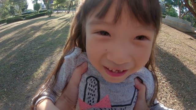 幸せな小さな女の子が彼女の父親と一緒に遊んで - 校庭点の映像素材/bロール