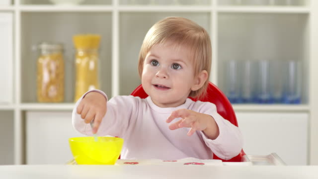 hd: happy little girl playing with spoon and bowl - one baby girl only stock videos & royalty-free footage