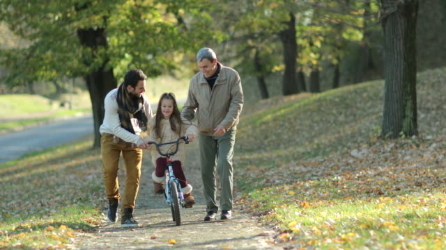 Happy little girl riding bicycle with help of father and grandfather.