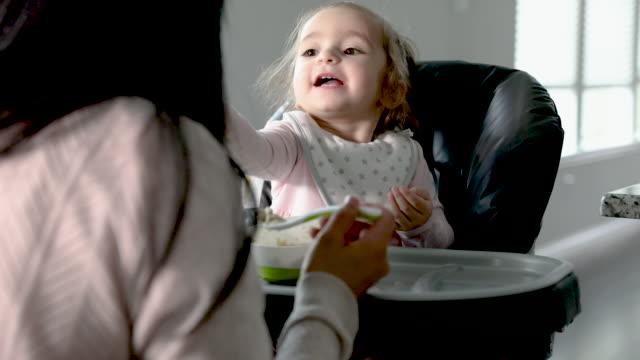 vidéos et rushes de la petite fille heureuse emploie la cuillère pour manger les céréales instantanées tout en s'asseyant dans la chaise haute - céréale