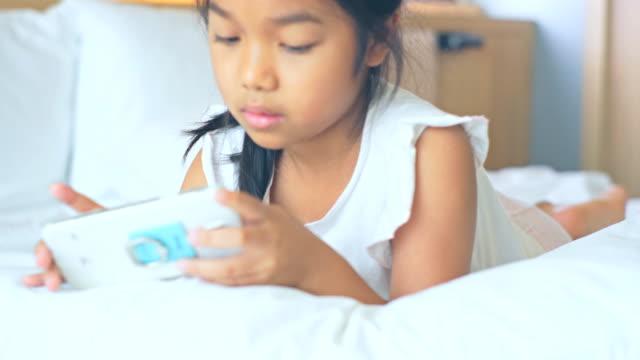 寝室で携帯電話を使用して幸せな小さな女の子。 - 寝室点の映像素材/bロール