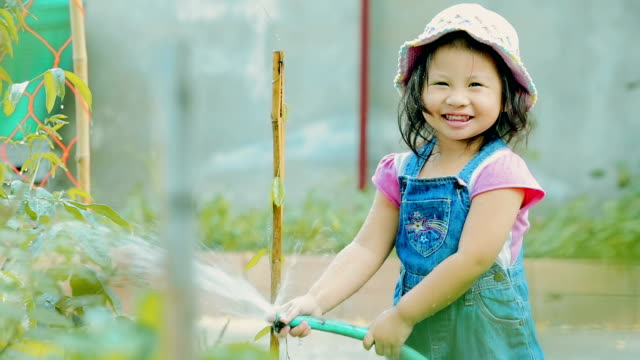 Happy little girl watering plant in garden \\ Concept : taking care of nature