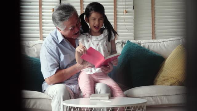 stockvideo's en b-roll-footage met gelukkig klein meisje met grootvader lezen verhaal boek thuis. gezinnen in hong kong - 1991