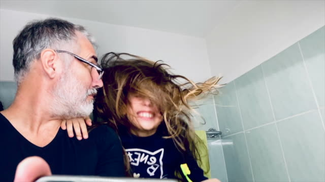 happy little girl with long hair rocking her head while in bathroom with father - rebellion stock videos & royalty-free footage