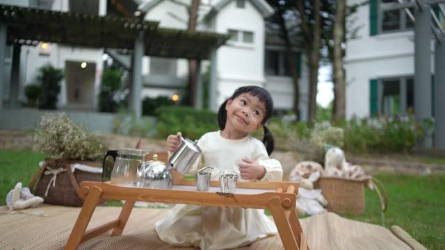 ็snackt litet barn gör kaffe i trädgården. - het dryck bildbanksvideor och videomaterial från bakom kulisserna