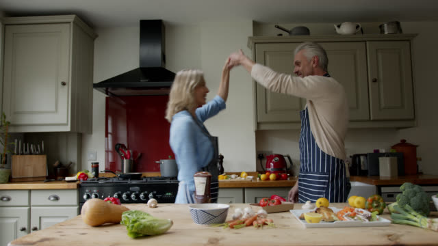 happy loving couple enjoying date night cooking at home and dancing - mature couple stock videos & royalty-free footage