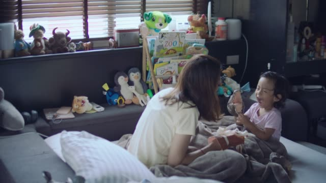 happy loving family. mother and her daughter in kids room. funny mom and lovely child having fun and playing performance in the puppet theater indoors. doll and teddy bear. - pupazzo video stock e b–roll
