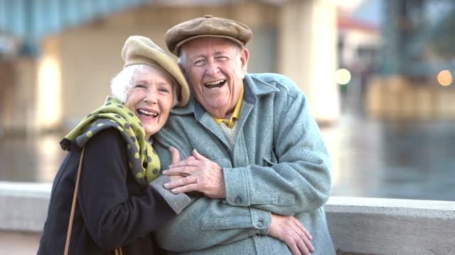 stockvideo's en b-roll-footage met gelukkig, liefdevolle senior paar dragen van jassen en hoeden - 70 79 jaar