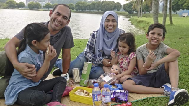 happy malay family enjoying in the park - islam stock videos & royalty-free footage
