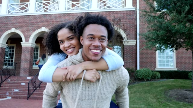 happy male college student carries his girlfriend on his back - flirting stock videos & royalty-free footage