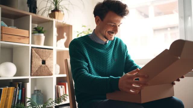 自宅で幸せな男性の顧客の開口部配達パッケージ - 贈り物点の映像素材/bロール