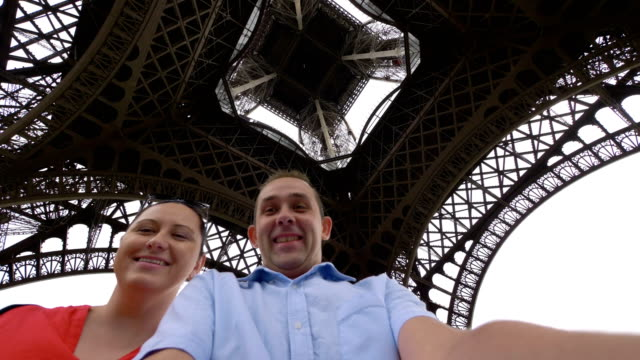 Happy man and woman spinning and having fun under the Eiffel Tower in Paris in slow motion in 4k