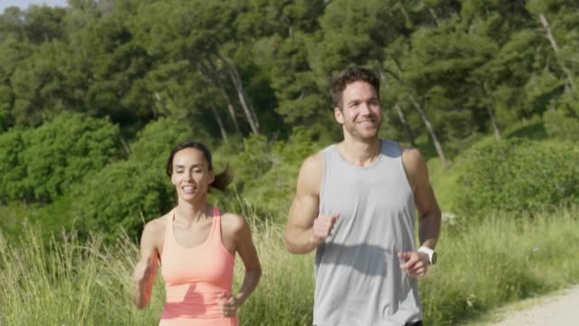 happy man and woman talking while jogging at park - routine stock videos & royalty-free footage