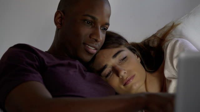 Happy Man And Woman Using Laptop On Bed