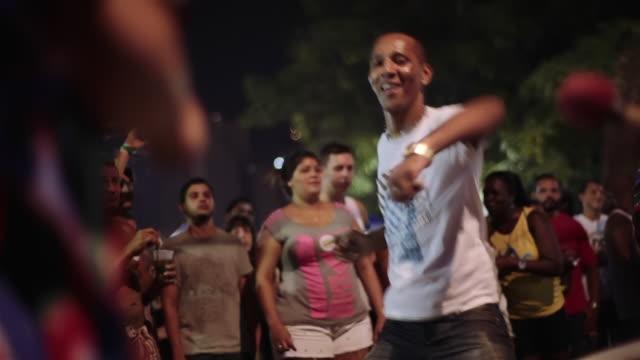 Happy man dances to Brazilian samba drumline