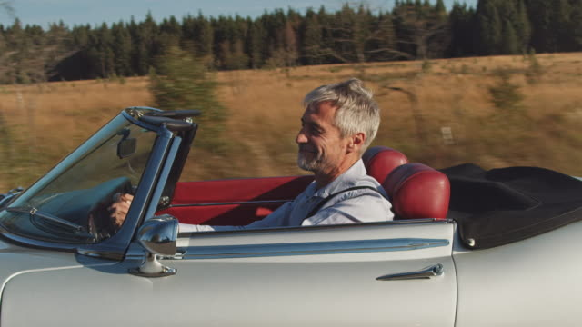 happy man driving vintage car during summer - classic car stock videos and b-roll footage