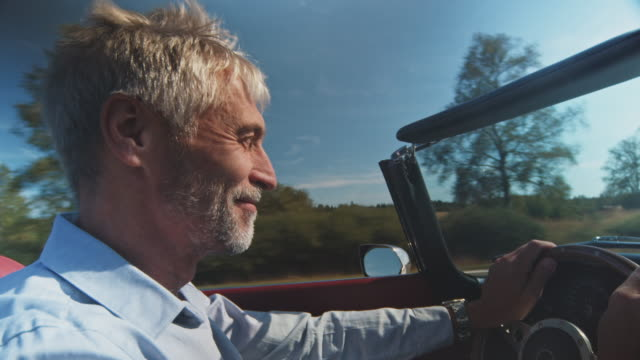 vídeos de stock e filmes b-roll de happy man driving vintage car on sunny day - cabelo grisalho