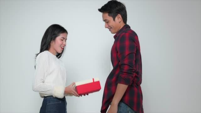 vidéos et rushes de homme heureux donnant le présent dans la boîte de cadeau à la femme dans le coup de ralenti - cadeau