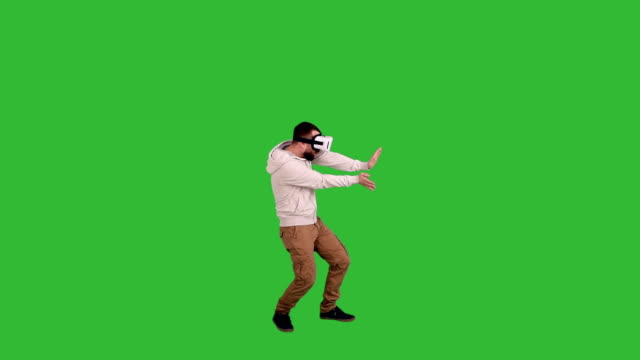 happy man in glasses virtual reality boxing on a green background - illusion stock videos & royalty-free footage